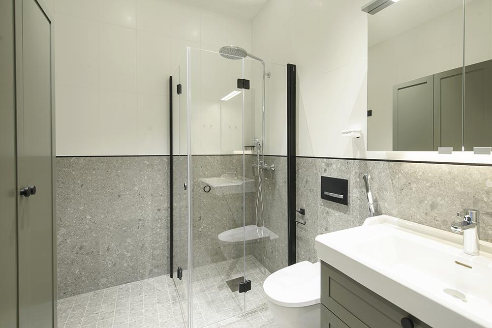 Kaunis uusittu kylpyhuone, jossa harmaata laattaa, valkoista laattaa ja kalusteissa kaunista vihertävää oliivin sävyä.